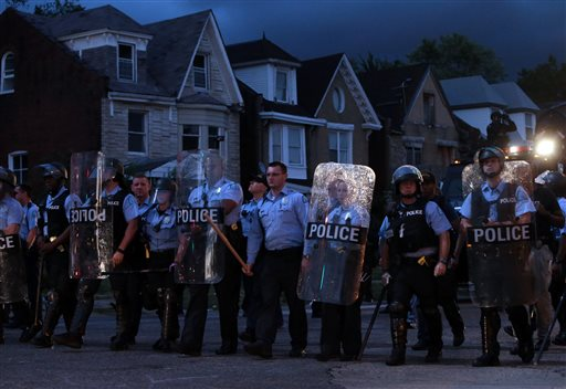 Police in riot gear stand guard as protesters gather Wednesday, Aug. 19, 2015, in St. Louis. A black 18-year-old fleeing from officers serving a search warrant at a home in a crime-troubled section of St. Louis was fatally shot Wednesday by police after he pointed a gun at them, the city's police chief said. (Laurie Skrivan/St. Louis Post-Dispatch via AP)