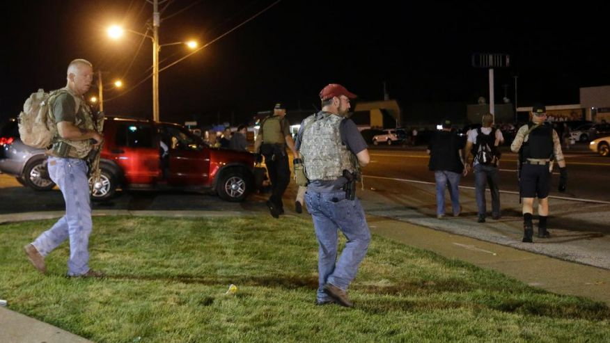 """Heavily armed civilians with a group known as the Oath Keepers arrive in Ferguson, Mo., early Tuesday, Aug. 11, 2015. The far-right anti-government activists, largely consists of past and present members of the military, first responders and police officers. St. Louis County Police Chief Jon Belmar said the overnight presence of the militia group, wearing camouflage bulletproof vests and openly carrying rifles and pistols on West Florissant Avenue, the hub of marches and protests for the past several days, was """"both unnecessary and inflammatory."""" (AP Photo/Jeff Roberson)"""