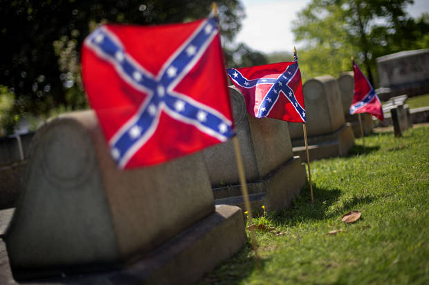 Confederate flags are planted next to the graves of Confederate soldiers in Oakland cemetery, Monday, April 22, 2013, in Atlanta. Georgia observes Confederate Memorial Day Monday marking the anniversary of the end of the Civil War. While April 26th is officially recognized as Confederate Memorial Day, state offices are closed Monday in observance of the holiday. (AP Photo/David Goldman)