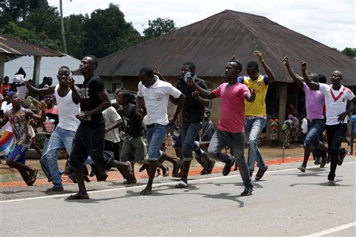 In this photo taken Friday, Aug. 14, 2015, people celebrate being released from Ebola quarantine, after Sierra Leone President Ernest Bai Koroma cut a tape to release the quarantine in the village of Massessehbeh on the outskirts of Freetown, Sierra Leone.  Five months after a man traveled to his home village for festivities marking the end of Ramadan, and died suddenly from Ebola, but now President Koroma came to cut down the fencing to mark the formal end of Sierra Leone's largest remaining Ebola quarantine. (AP Photo/Sunday Alamba)