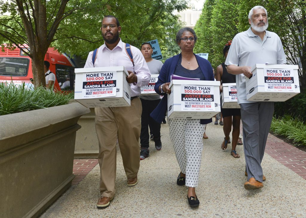 (Left-Right) Eugene Puryear of the Stop Police Terror Project in Washington, D.C., Lois Wilkins, the Freeland, Mich., resident and mother of four who started the petition on MoveOn.org, and Reverend Graylan Hagler, the senior pastor of the Plymouth Congregational United Church of Christ carry boxes of signed petitions to the visitor's entrance of the Department of Justice. (Freddie Allen/NNPA News Wire)