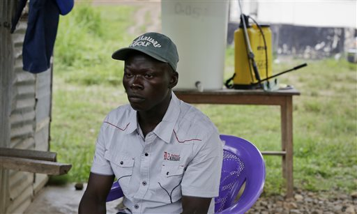 """In this Monday, Aug. 10, 2015 photo, Juma Musa describes how he once opened a batch of ineffective chlorine powder that had expired a year earlier, during an interview at the government hospital in Kenema, eastern Sierra Leone. In the background is a yellow chlorine disinfectant sprayer. More than 40 health workers at the facility have died of Ebola. """"We were in a war zone and the chlorine was the only thing that was giving us courage to come closer to patients,"""" Musa says. (AP Photo/Sunday Alamba)"""