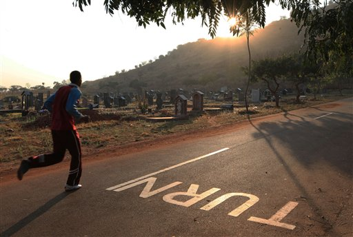 In this photo taken Saturday July 25, 2015, a jogger passes  through the Warren Hills Cemetery in Harare. Due to lack of gyms and other exercise venues in many Harare neighborhoods, the cemetery has become a workout site for many fitness enthusiasts. (AP Photo/Tsvangirayi Mukwazhi)