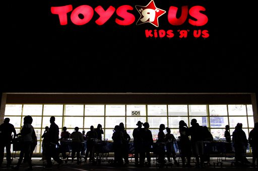This Nov. 25, 2010, file photo shows people lining up outside Toys R Us as Black Friday sales begin in Royal Palm Beach, Fla. Toys R Us said Wednesday, Sept. 16, 2015,  it won't hire as many holiday season employees as it did last year, but the toy and baby products retailer says it will give current employees and seasonal workers a chance to work more hours. (Rachel Mummey/Palm Beach Post via AP, File)
