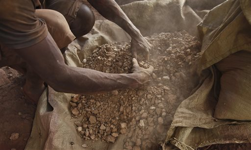 In this photo taken Wednesday, Aug. 19, 2015, a Ugandan gold miner sorts gold ore before it is loaded into a milling machine, in the Mubende district west of the capital Kampala, in Uganda. The gold rush is on in a big way in the Ugandan district of Mubende, with tens of thousands of people making their livelihood from it. (AP Photo/Stephen Wandera)