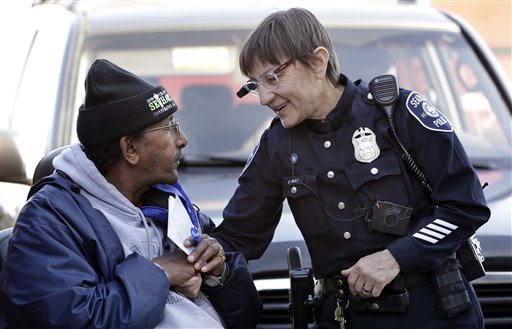 In this March 12, 2015, file photo, Seattle police officer Debra Pelich, right, wears a video camera on her eyeglasses as she talks with Alex Legesse before a small community gathering in Seattle. The camera is attached to a battery pack and controls on the officer's uniform. The use of police body cameras is spreading to keep officers honest about using force against citizens. But how and when the public gets to see the footage is up for debate. (AP Photo/Elaine Thompson, File)