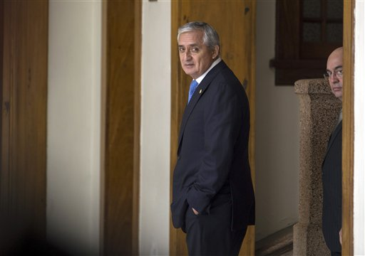 Guatemala's President Otto Perez Molina, center, leaves a press conference followed by his spokesman Jorge Ortega, in Guatemala City, Monday, Aug. 31, 2015. The head of Guatemala's congress says that lawmakers would decide on Tuesday whether to lift Perez Molina's immunity from prosecution in a corruption case, as recommended by a legislative committee. (AP Photo/Luis Soto)