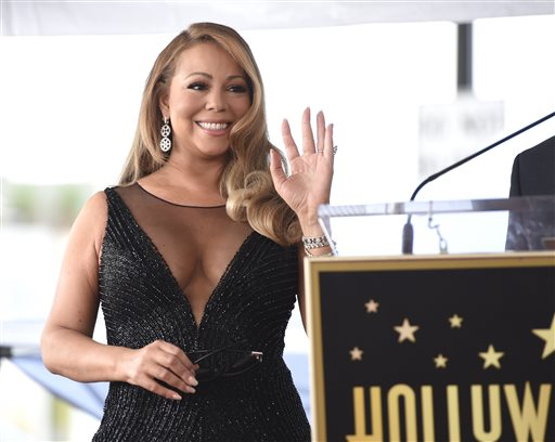 "In this Aug. 5, 2015 file photo, Mariah Carey attends a ceremony honoring her with a star on the Hollywood Walk of Fame in Los Angeles. A Cincinnati film commission has announced that pop singer Carey will be filming a Christmas movie in the region. WCPO-TV reports the Greater Cincinnati Film Commission said Tuesday, Sept. 15, 2015, the singer and actress is set to star in ""Melody & Mistletoe"" in Cincinnati starting in October. (Photo by Chris Pizzello/Invision/AP, File)"