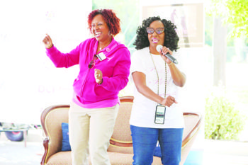 Dr. Regina Hampton, a general surgeon at Doctors Community Hospital, and Victorianne Russell-Walton of It's in the Genes pumps up the crowd at a P.I.N.K.I.E. party for Breast Cancer Awareness Month in Lanham, Maryland, in October. (Courtesy of Doctors Community Hospital)