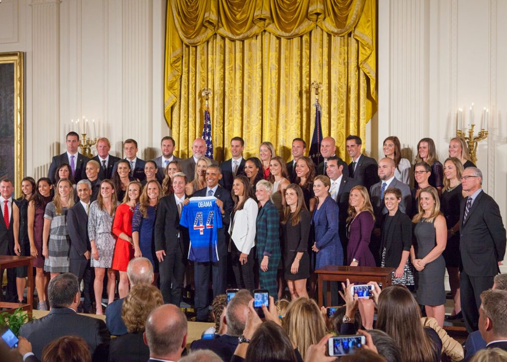 """President Obama welcomed the United States Women's National Soccer Team to the White House to honor the team and their victory in the 2015 FIFA Women's World Cup. The team presented Obama with a jersey with the number 44 on it. The FIFA trophy sits on a table next to the podium. """"These champions deserve all the attention they've been receiving,"""" Obama said. (Cheriss May/HUNS)"""