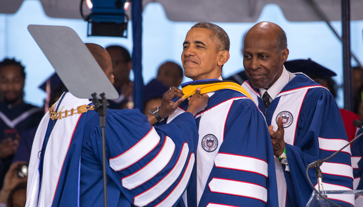President Wayne A. I. Frederick (left) adjusts President Obama's hood as civil rights icon Vernon Jordan looks on during the 2016 Howard University Commencement ceremony on May 7, 2016 in Washington, D.C. President Obama received an honorary science doctorate for his work on the Affordable Care Act. (Cheriss May/HUNS)
