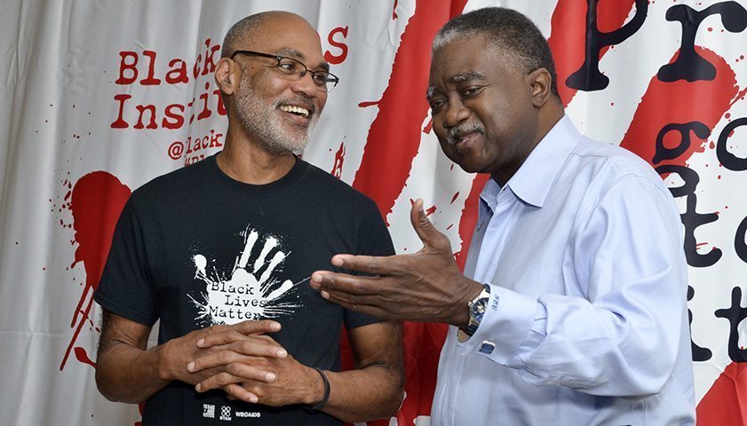 Phill Wilson (left), the executive director of the Black AIDS Institute, talks to George Curry at the 2016 International AIDS Conference in Durban, South Africa. (Freddie Allen/AMG/BAI)
