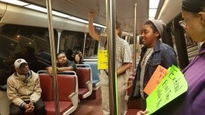 Maryland state Delegates Erek Barron (left, in foreground) and Carlo Sanchez (sitting behind Barron) ride a Metro train on the Green Line with a small group of residents who want the transit agency to extend its late-night rail service. PHOTO BY WILLIAM J. FORD