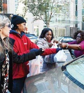 Shelia Turner (right) gives bags of food for her donation to NBC4 anchor Pat Lawson-Muse during the Food for Families drive in northwest D.C. on Nov. 21. PHOTO BY ROY LEWIS