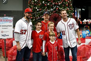 Washington Nationals baseball players Tanner Roark (left) and Max Scherzer (right) greet fans who won the opportunity by gifting toys and entering a raffle drawing during the team's annual Winterfest event at the Walter E. Washington Convention Center in Northwest on Saturday, Dec. 10.