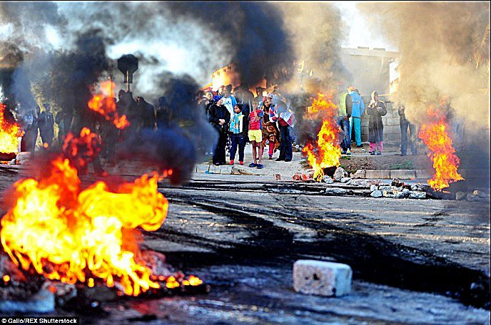 Parents and pupils block a road with burning tyres during violent protests over the closure of 33 schools in Port Elizabeth, South Africa. /Courtesy of Gallo/REX Shutterstock
