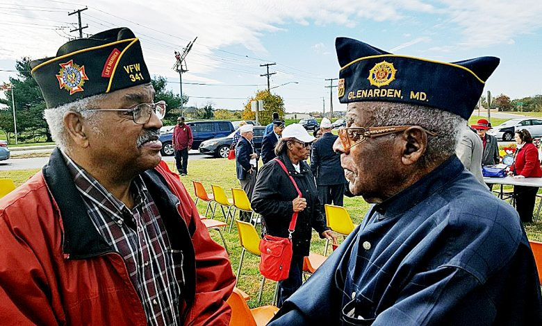 Military veterans Allen White (left) and Curtis Parker greet each other after an annual Veterans Day commemorative event at the Peace Cross in Bladensburg, Maryland, on Nov. 11. /Photo by William J. Ford