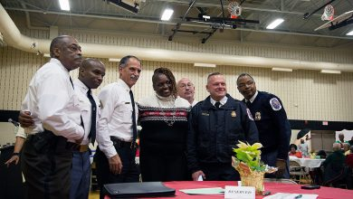 """From left: Prince George's County Sheriff Melvin High, Deputy Chief Raphael Grant, Fire Chief Marc Bashoor, PGF/EMS Batallion Chief C.H. Hunt, Assistant Fire Chief Alan Doubleday, and Capt. Kevin Hughes pose with local resident Anna Godfrey at the fifth annual """"District 7 Review"""" and dessert reception at Hillcrest Heights Community Center on Dec. 18."""