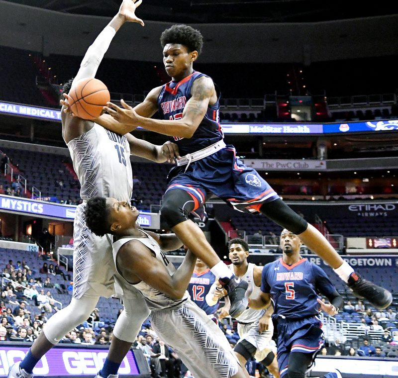 Howard Bison guard Charles Williams barrels into two Georgetown Hoyas defenders on a drive to the basket in the first half of the Hoyas' 85-72 win at Verizon Center in Northwest on Sunday, Nov. 27. /Photo by John E. De Freitas