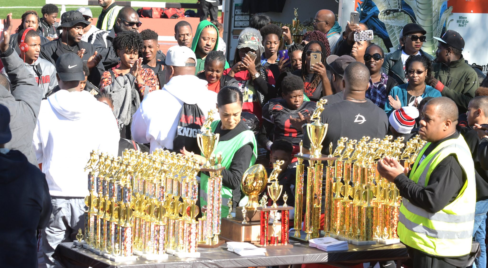 Fans and parents join game participants for the trophy presentation following the championship game for the 10U division of American Youth Football's Capital Beltway League at Spingarn High School Field in northeast D.C. on Saturday, Nov. 5.