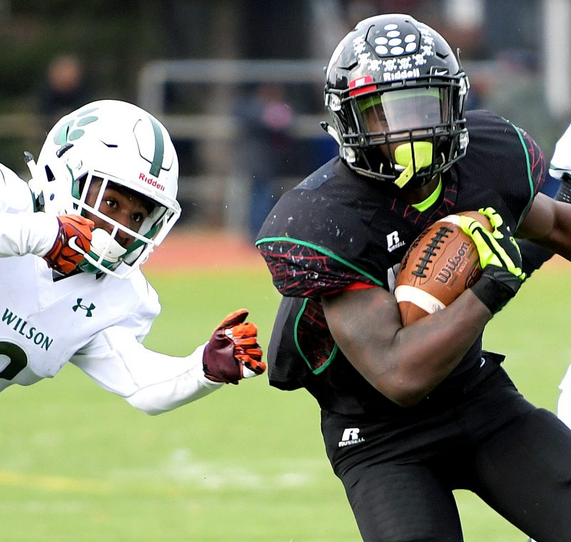 H.D. Woodson running back Mychale Salahuddin evades Wilson defensive back Sean Savoy in the first quarter of Woodson's 22-20 win in the 47th annual DCIAA Turkey Bowl Football championship game at Eastern High School in northeast D.C on Thursday, Nov. 24. /Photo by John E. De Freitas