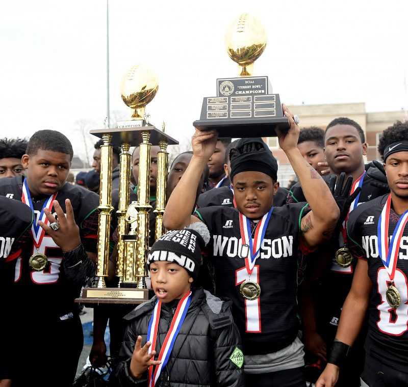 Players on the H.D. Woodson High football team celebrate after a 22-20 win over Wilson High in the 47th annual DCIAA Turkey Bowl Football championship game at Eastern High School in northeast D.C on Thursday, Nov. 24. /Photo by John E. De Freitas