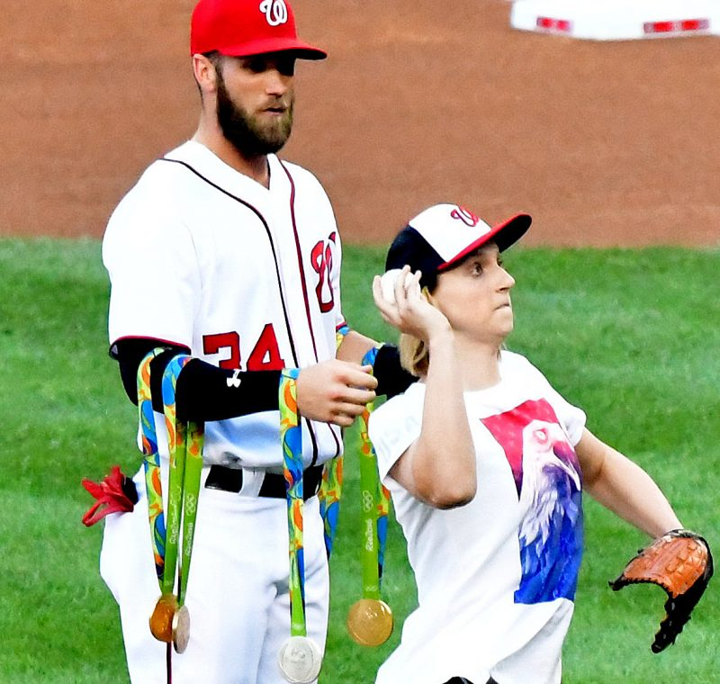 World champion swimmer and Maryland native Katie Ledecky, who won four gold medals at this summer's Rio Olympics, throws the first pitch before Washington Nationals-Baltimore Orioles game at Nationals Park in southeast D.C. on Wednesday, Aug. 24 as Nationals right fielder Bryce Harper holds her medals. /Photo by John E. De Freitas