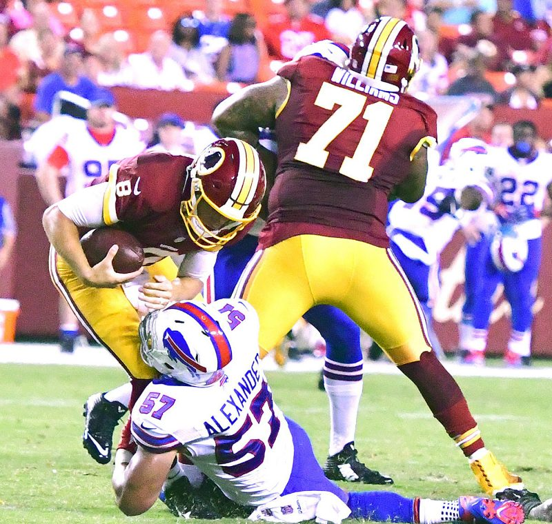 Washington Redskins quarterback Kirk Cousins is sacked by Buffalo Bills linebacker Lorenzo Alexander, which was negated by a penalty, in the first quarter of the Redskins' 21-16 preseason win at FedEx Field in Landover, Maryland, on Friday, Aug. 26. /Photo by John E. De Freitas