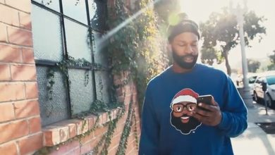 Former NBA superstar Baron Davis wears a sweater bearing his company's Black Santa logo.