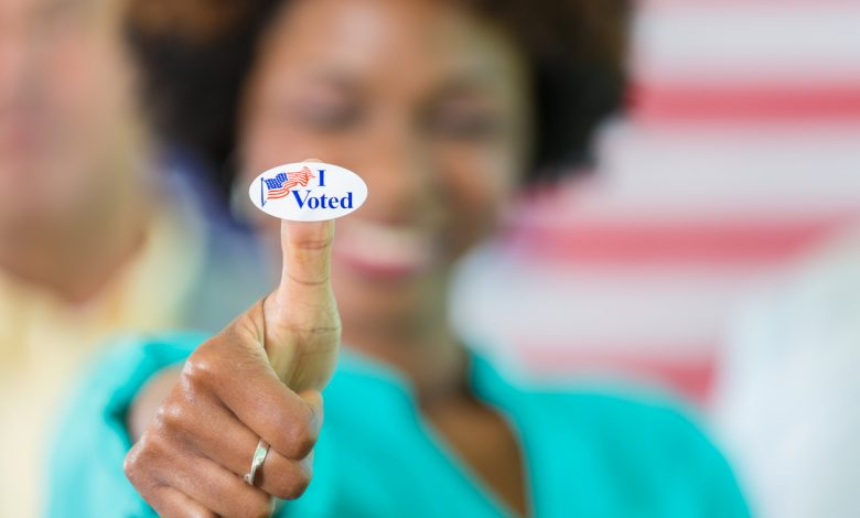 """Smiling african american woman with an """"I voted"""" sticker on her thumb. /Photo: iStock"""