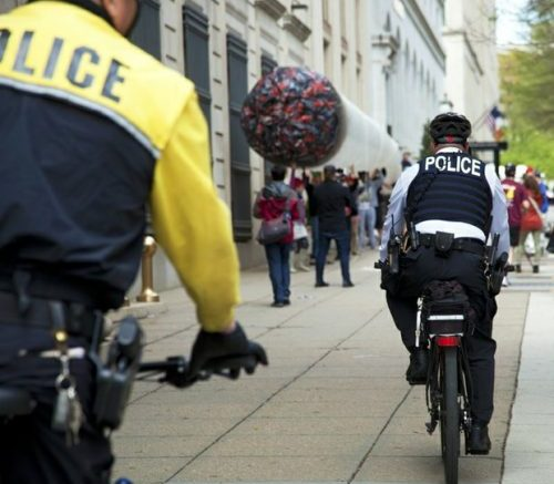 Members of the DC Metropolitan Police Department bicycle unit ride up 15th Street Northwest to greet the protesters carrying a 50-foot inflated marijuana joint down the street. /Photo by Nancy Shia @nancy_shia