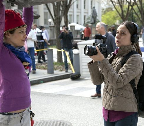 DC marijuana activist Erica Madrid (left) is interviewed by the media while she helps hold up the 51-foot giant inflated joint. /Photo by Nancy Shia @nancy_shia