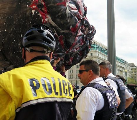 Members of law enforcement face off with the giant joint on Pennsylvania Avenue Northwest Saturday, April 2, 2016. /Photo by Nancy Shia