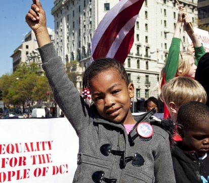 Six-year-old DC resident Lakaiela Dolmon waves the flag of DC from the stage in Freedom Plaza at a protest against federal taxation without representation and a rally for DC Statehood Friday, April 15, 2016. /Photo by Nancy Shia @nancy_shia