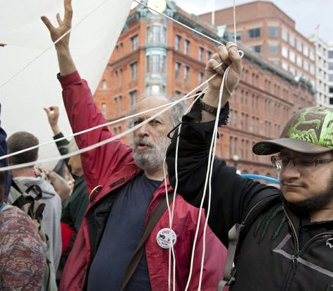 Retired Howard University mathematics professor David Schwartzman (center) helps carry a giant 51-foot joint at a demonstration calling for the de-scheduling of marijuana to be legal. /Photo by Nancy Shia @nancy_shia