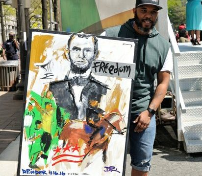 """Artist Demont """"Peekaso"""" Pinder displays his artwork that was painted during the Emancipation Day Parade on Saturday, April 16, 2016 in Northwest. /Photo by Patricia Little @5feet2"""