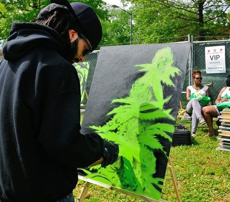 Artist Jah-One (Nessar Jahanbin) paints a marijuana leaf on canvas during the National Cannabis Festival on Saturday, April 23, 2016 at RFK Stadium in northeast DC. /Photo by Patricia Little @5feet2