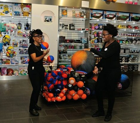Employees Teresa Hamilton (left) and Devonne Johnson (right) have fun with store merchandise during the grand opening of Dave and Buster's restaurant, Monday, April 25, 2016 in Capitol Heights, MD. /Photo by Patricia Little @5feet2