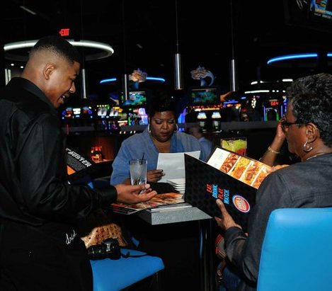 A waiter assists patrons with menu selections during the grand opening of Dave and Buster's restaurant, Monday, April 25, 2016 in Capitol Heights, MD. /Photo by Patricia Little @5feet2