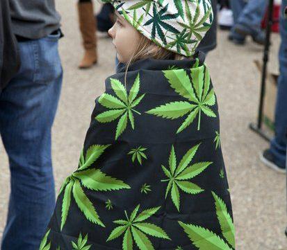 An unidentified child wears the Phrygian had and drapes herself in a marijuana flag. /Photo by Nancy Shia @nancy_shia