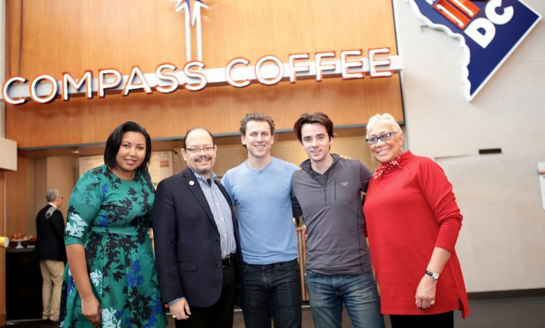 Alexander M. Pedro, executive director of Shaw Main Streets, Compass Coffee co-founders Michael Haft and Harrison Suarez, and Gretchen Wharton join city officials on Jan. 12 to celebrate the opening of D.C.'s homegrown coffee shop Compass Coffee in the lobby of the Walter E. Washington Convention Center in Northwest. (Demetrious Kinney)