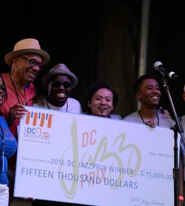 DCJazzFest: Sunny Sumter, 1st and Willard Jenkins 2nd present a 15,000.00 check to the Band that won the Best Band contest, on Saturday June 18 2016 in Southeast DC. /Photo by Roy Lewis