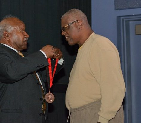 Nat Whitmyer (right), class of 1958, receives the Living Legend Medal as a former football player at Paul Lawrence Dunbar high school during the world premiere screening of Dunbar, Thursday, March 31, 2016 at the E Street Cinema in Northwest. /Photo by Patricia Little @5feet2