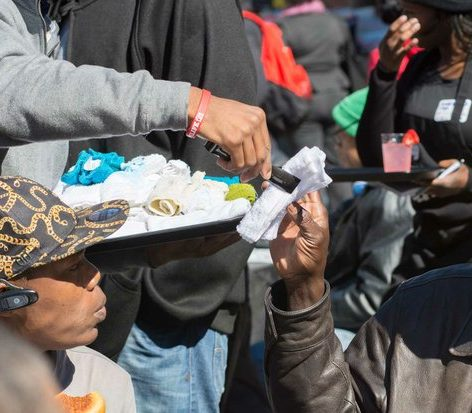 A volunteer passes out warm hand tiles to residents at the New York Avenue men's shelter during during Sunday Soul DC Pop Up at the New York Avenue men's shelter, Sunday, April 3, 2016 in Northeast DC. /Photo by Patricia Little @5feet2