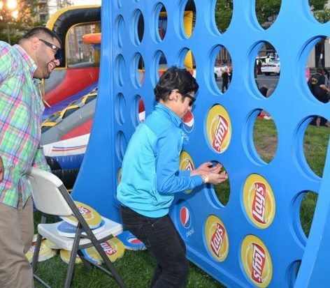 A father and son enjoy playing a life game of Connect 4 during the custom competition at the Cherry Blast event on Saturday, April 16, 2016 at the Carnegie Library in northwest. /Photo by Patricia Little @5feet2