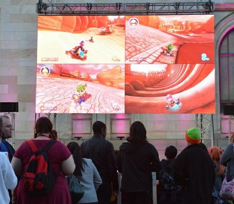 Attendees catch a glimpse of gaming activities on the big screen during the custom competition at the Cherry Blast event on Saturday, April 16, 2016 at the Carnegie Library in northwest. /Photo by Patricia Little @5feet2
