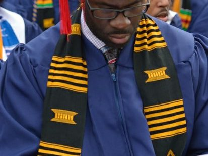 A student looks for his name in the program booklet during the 148th Commencement Convocation at Howard University on Saturday, May 7, 2016 in Northwest. /Photo by Patricia Little @5feet2