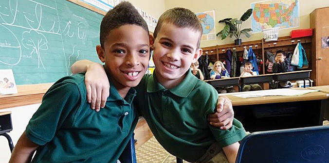 Students like these two young boys find that there are benefits in learning and playing together – even when you're from two different cultures. /Photo by Urban News Service
