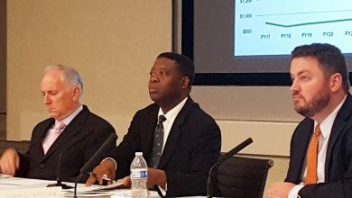 Metro Chief Financial Officer Dennis Anosike (center) briefs the agency's finance committee on Oct. 13 about its $275 million budget shortfall. /Photo by William J. Ford