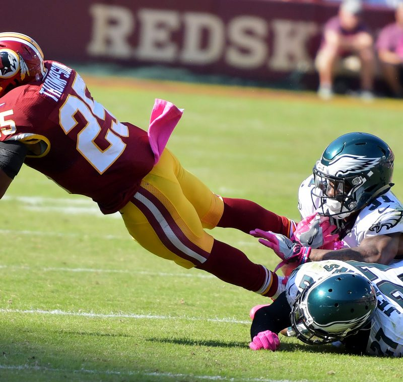 Washington Redskins running back Chris Thompson is tackled by two Philadelphia Eagles defenders during the Redskins' 27-20 win at FedEx Field in Landover, Maryland, on Sunday, Oct. 16. /Photo by John E. De Freitas